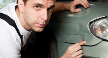 5625879 - close-up of damaged car inspected by mechanic